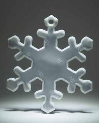 Glimmering white snowflake. Comes with a chrome ball chain.  Attach to bags, jackets or any other garments or equipment.  Approximately 70 mm high and wide.  For maximum visibility place on the front, side or back of your body. Allow your reflector to move freely at knee length to catch the headlights of moving vehicles.