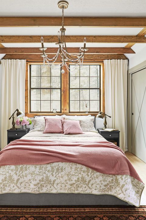 After—Master Bedroom:  Jenna secured the curtain rod to a wood beam and hung cotton sheers to flank the windows. A pretty chandelier and simple toile bedding add a feminine touch to the rustic space.