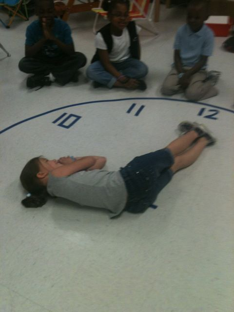 Teaching time by doing!  Many kids learn by doing so having them use their bodies to make the time would be a benefit to them.  Let them figure out how to move their body to get the correct time.  Use a hula hoop and put tape around it and tape the numbers to the floor with masking tape.