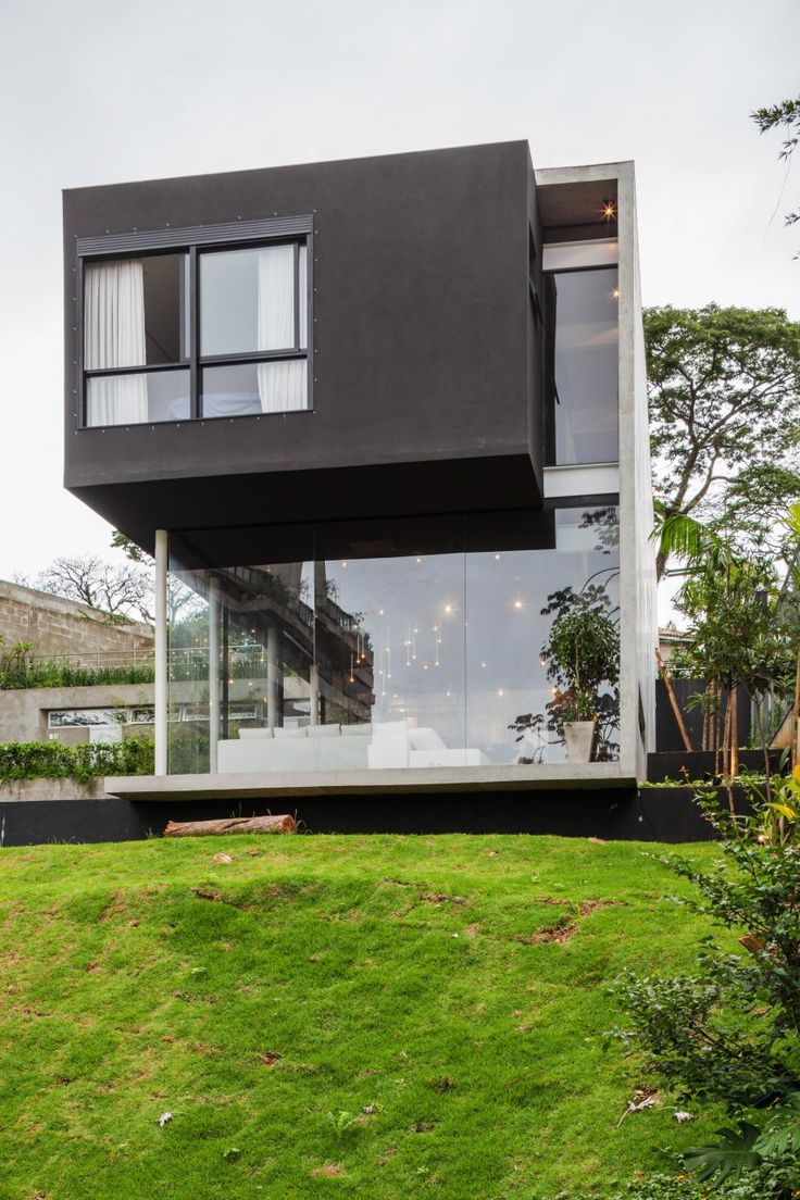 Brazilian firm FGMF Arquitetos has built a São Paulo home around a steel frame embedded into a concrete wall, allowing the use of extensive glazing that offers views down a verdant hillside.