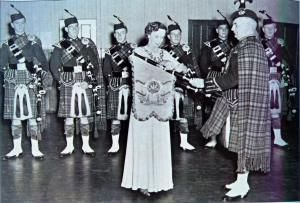 PM Ackroyd of the Second Battalion Transvaal Scottish being presented with a pipe banner by the Colonel's wife Mrs Norma Thompson in 1946.