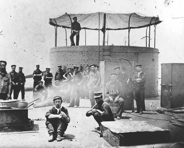 One hundred and fifty-one years after the Civil War ship the USS Monitor sank off the North Carolina coast, two unknown crewmen found in the ironclad's turret were buried Friday evening at Arlington National Cemetery.    This 1862 photo provided by The Mariners' Museum shows crew sitting on the deck of the Civil War ironclad USS Monitor.
