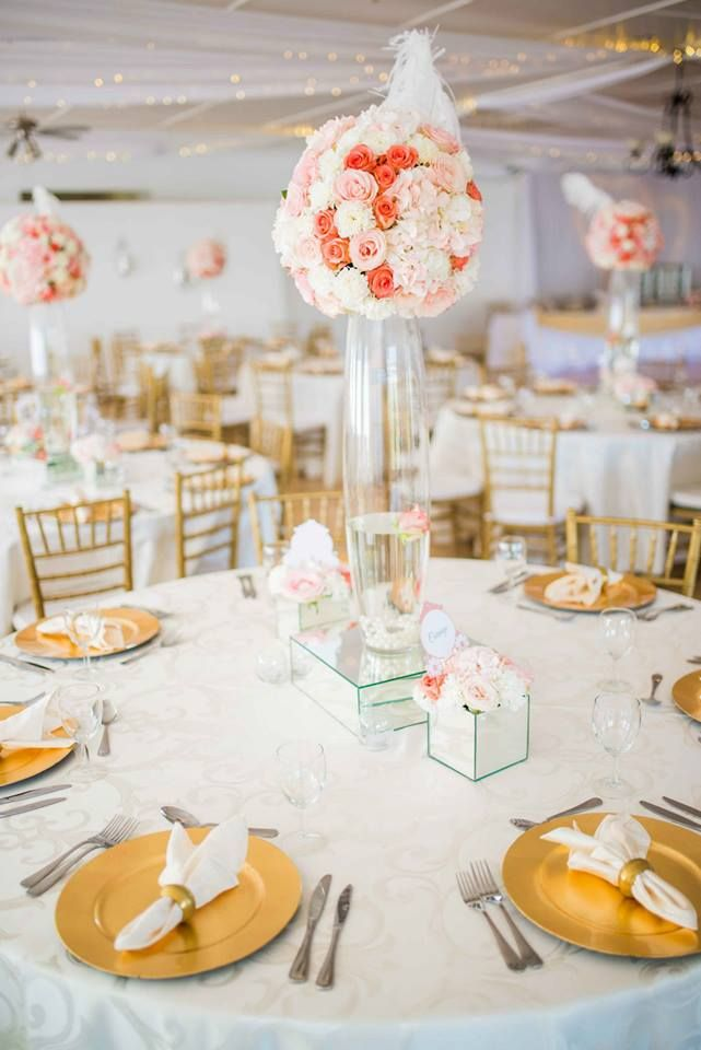 Monte Vista Venue peach and gold table setup with a white tablecloth, gold under plates, gold tiffany chairs and a peach medium arrangement centerpiece in a bullet vase on a mirror box and two small mirror boxes with flowers in on either side.