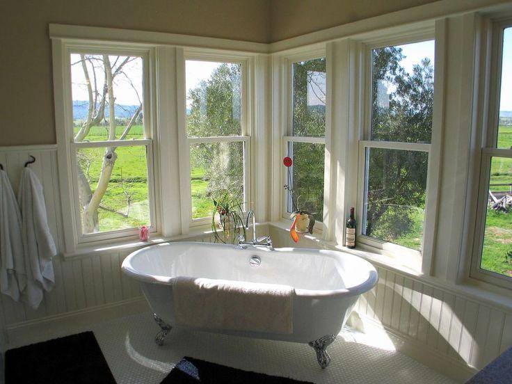 Landelijke badkamer met een geweldig uitzicht. Dit is werkelijk een droom van een landelijke badkamer! Een badkamer met aan twee kanten ramen is al zeer fraai, maar met uitzicht op de weilanden is natuurlijk fantastisch! De verchroomde versierde pootjes van het bad geven de ruimte een romantisch accent.