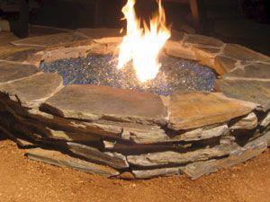 Outdoor fire pit ideas using fire glass. Modern outdooor fireplace designs using burning glass.