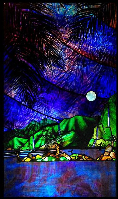 Stained glass window by Frank Errickson depicting tropical night scene with distant mountains and islands, waves, waterfalls, and palm leaf silhouettes.