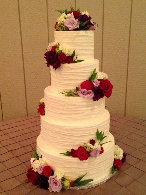 Rustic, rough textured buttercream wedding cake with fresh flowers