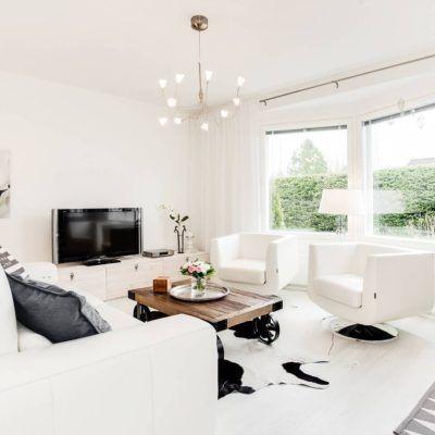 Puinen kärrypöytä ja modernit valkoiset nojatuolit tuovat olohuoneen sisustukseen kivaa kontrastia.