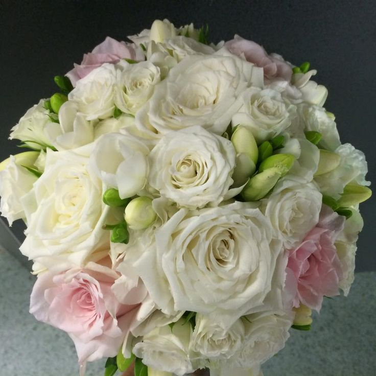 White & some pale pink roses, white spray roses, lisianthus & freesias create this delicate posy - top view