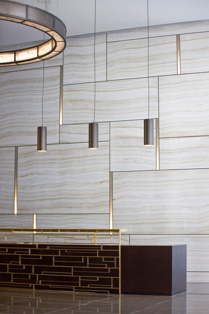 Brass Grouting. Who said grouting was boring. Marble and brass- great combination. Large tiles of stone in few sizes- simple but interesting. I like the lighting- simple pendant lamps over the reception desk. However how would they work together with a large logo sign on the wall?