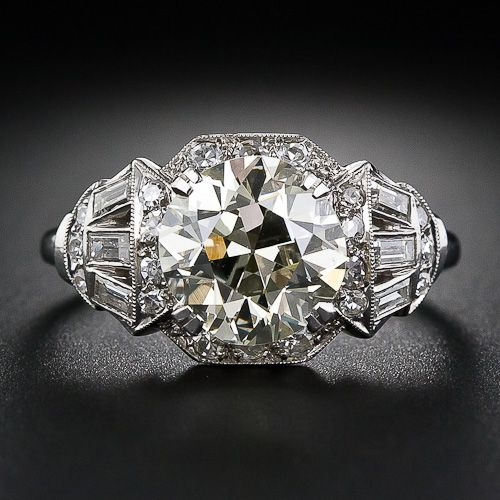 This beautiful, bright and splashy original Art Deco ring, superbly handcrafted in platinum, circa 1930s, radiates with a warmly tinted European-cut diamond weighing 3.00 carats. The gorgeous and virtually flawless diamond radiates from a stylized diamond-set octagonal setting which artfully transitions into a shimmering fan of baguette diamonds, creating a spectacular, sophisticated and singular Art Deco engagement ring.