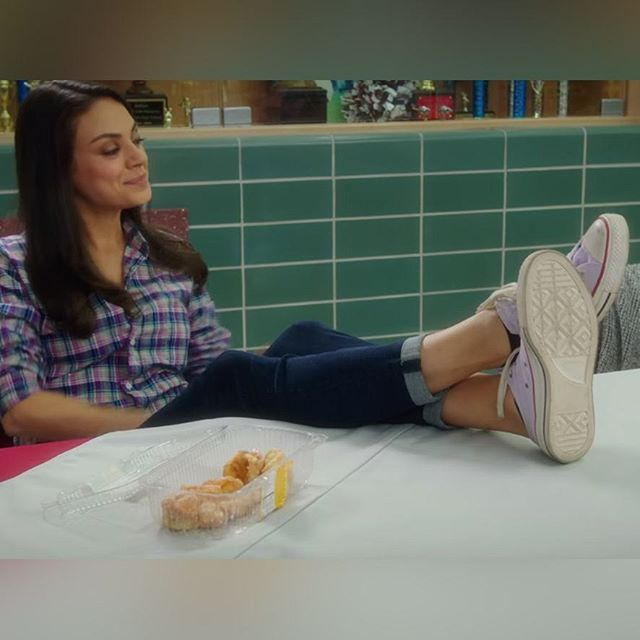 The white Converse shoes that Mila Kunis (Amy Mitchell) wears in the movie Bad Moms (2016).