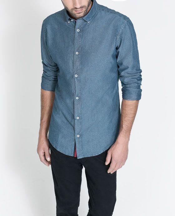 El hombre lleva una camisa azul. Esa camisa está en medio de informal y formal. Puedes ir a trabajar en la camisa, y ir al parque. La camisa es no especial, pero la camisa no cuesta demasiado dólares y la camisa es buena.