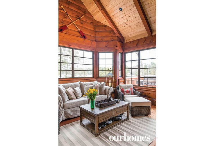 """The Muskoka room with screened windows is a quiet place to enjoy the fresh spring breezes while escaping the black flies.    See more of this home in """"Fifth Generation Legacy on Muskoka's Moon River"""" from OUR HOMES Muskoka Early Summer 2017: http://www.ourhomes.ca/articles/build/article/fifth-generation-legacy-on-muskokas-moon-river"""