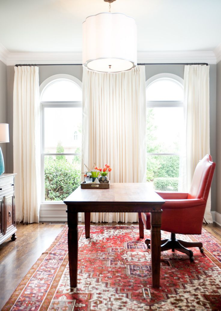 The red leather chair is a dynamic punch of color against the gray and white decor.
