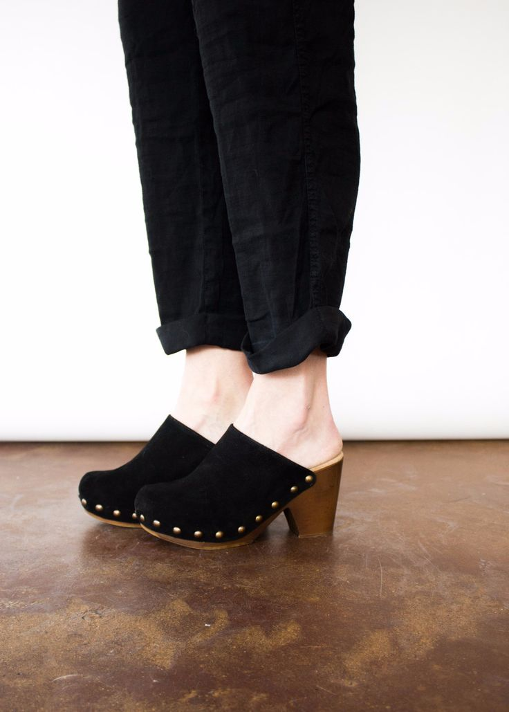 This classic suede clog features a rounded toe, metal stud detailing, and a  wooden