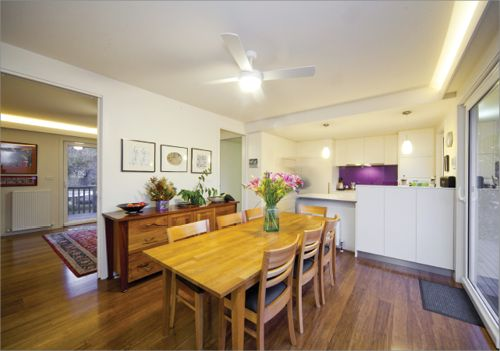 The inside of a Canberra home's living area, with kitchen in the background. The living area has bamboo floorboards and a ceiling light and fan, with strips of lights fitted along the corners of the external wall's ceiling.