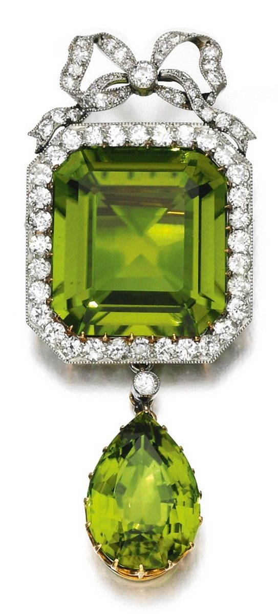 An antique peridot and diamond brooch, late 19th century. Designed as a step-cut peridot framed by circular-cut diamonds, beneath a bow motif, suspending a pear-shaped peridot. #antique #brooch