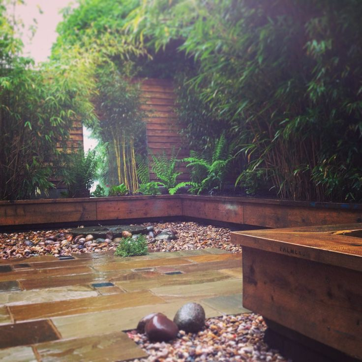 Scaffold board planters, sandstone paving and evergreen planting