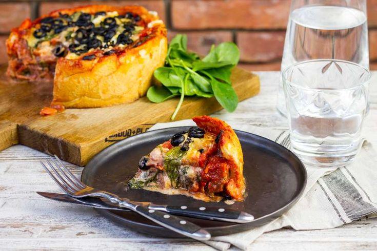 Recept voor pizzataart van salami en spinazie voor 4 personen. Met zout, boter, olijfolie, peper, bakpapier, pizzadeeg, verse spinazie, rode paprika, tomatensaus, tomaat, kruiden-roomkaas, chorizo, geraspte kaas en zwarte olijven