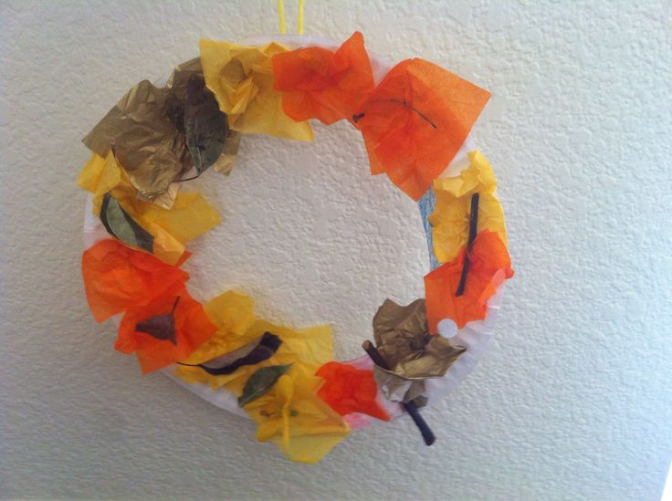 Fall wreath made by 4 year old, Abigail. Easy paper plate craft with colored, tissue paper squares, small sticks and dried leaves.