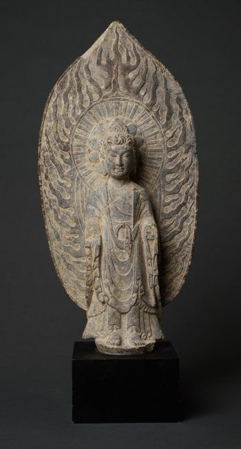 STANDING BUDDHA IN FRONT OF FLAMING NIMBUS Catalog Number: AB916-119 Grey stone China in the style of the Tang Dynasty HEIGHT (WITHOUT BASE) CA. 67 CM