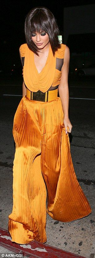 Pleats to see you: The voluminous fabric of the burnt orange garment draped over her figur...