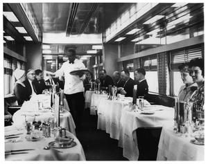 "Dinner is now being served aboard the Twin-unit dining car in the consist of the New York Central's ""Twentieth Century Limited"", circa 1960."