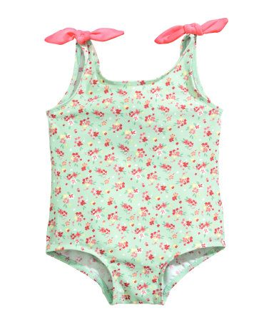 Mint green/floral. Swimsuit with a printed pattern, shoulder straps with decorative bows at top, and lined gusset.