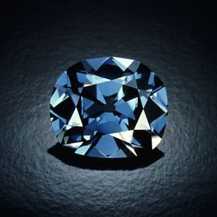 The Hope Diamond is one of the world's most famous gems - renowned for its nearly flawless clarity, rare deep blue color, and eventful history. It is surrounded by 16 white diamonds and suspended from a platinum chain bearing 46 more diamonds. This photograph was taken while the Hope was out of its current mounting.
