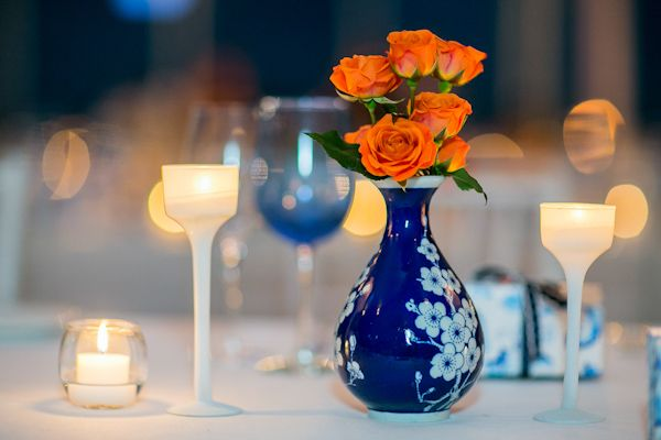 """Design tip: use complementary colors for a dynamic contrast. The orange roses really """"pop"""" against the contrasting blue vase. - Photo by Sarah Tew Photography"""
