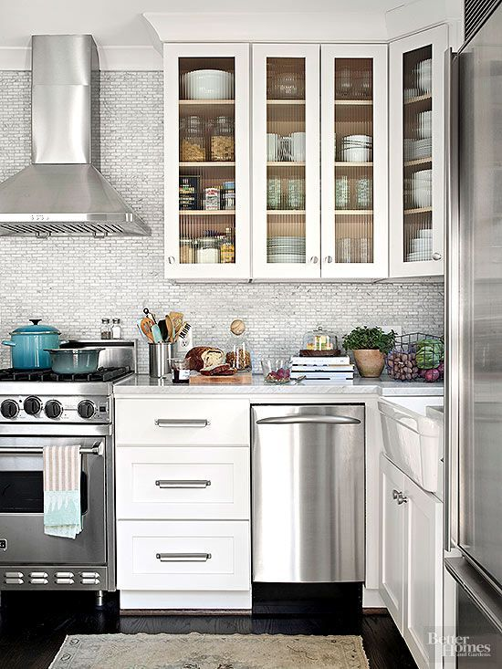 Trick #6: Slimmed down appliances, including a 24-inch-wide gas range and a 27-inch-wide refrigerator give the 8x11-foot kitchen an unexpected gourmet quality. Trick #7: Use texture to convey style. Ribbed glass (rather than clear glass or solid doors) becomes build-in decoration in a hard-to-decorate space. Inside, everyday dishes stand out like display pieces.