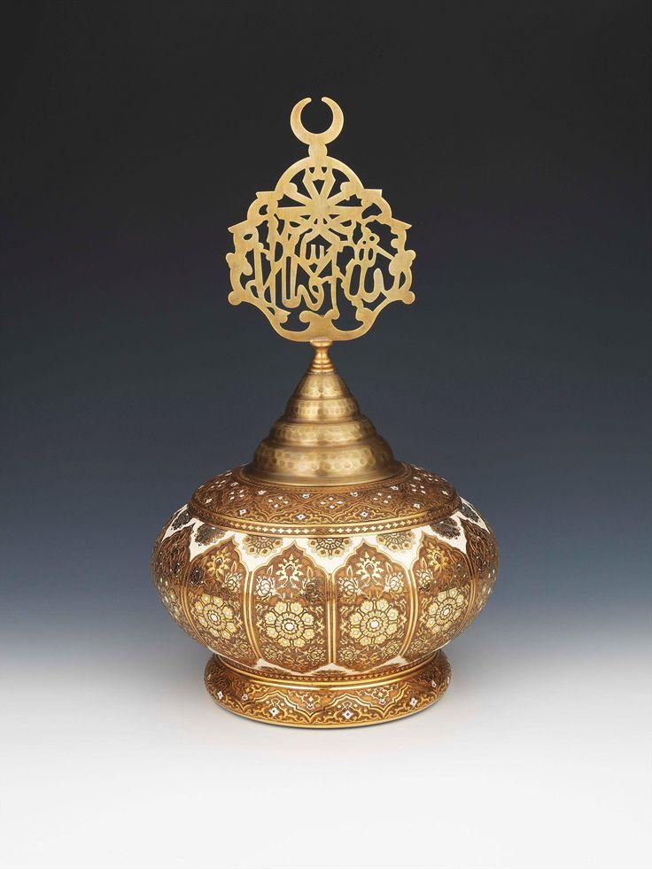"""Alemli Vazo-82113-1.250,00 TL (KDV dahil perakende satış fiyatı) Alemli Vazo'nun üretimi 2000 adet ile sınırlıdır. Alemli Vazo gövdesinde desen olarak, yanyana sıralanmış şemse motifleri içinde yer alan hatayi ve penç motifleri kullanılmıştır. Vazonun alem tepeliği ise Yeni Cami Valide Sultan Türbesinin 84 cm yüksekliğindeki metal aleminin bir replikasıdır. Orjinal alem Türk İslam Eserleri Müzesi'nde sergilenmektedir. Alemin üzerinde """"Lailaheillallah"""" ve çift """"Muhammed"""" yazmaktadır..."""