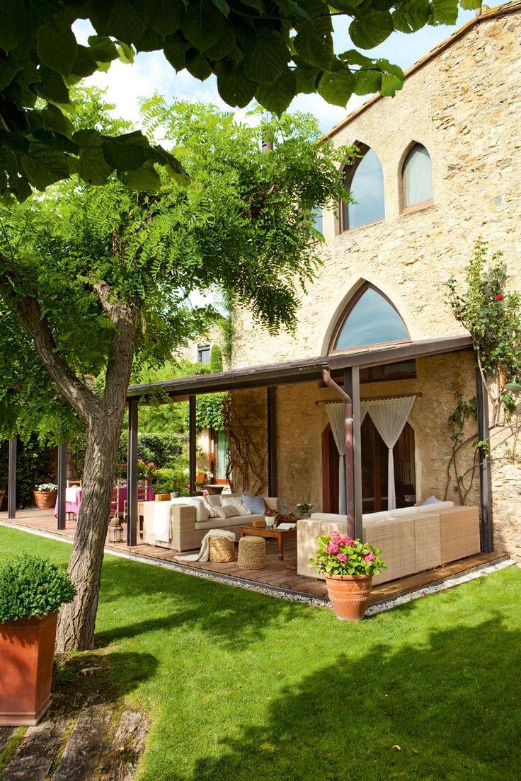 Los sofás de exterior son de la firmaDedony se equipan con cojines, de Cul de Sac. Los pufs de fibra natural son de Jordi Batlle. Las ventanas ojivales facilitan que el paisaje ampurdanés se cuele en la casa. El mueble