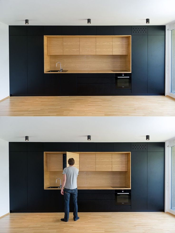 Black and wood as used here are entirely minimalist, with every kitchen item hidden carefully away in recessed cabinets.