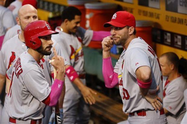 St. Louis Cardinals starting pitcher Adam Wainwright (50), right, and Matt Carpenter (13), left, horse around in the dugout before a basebal...