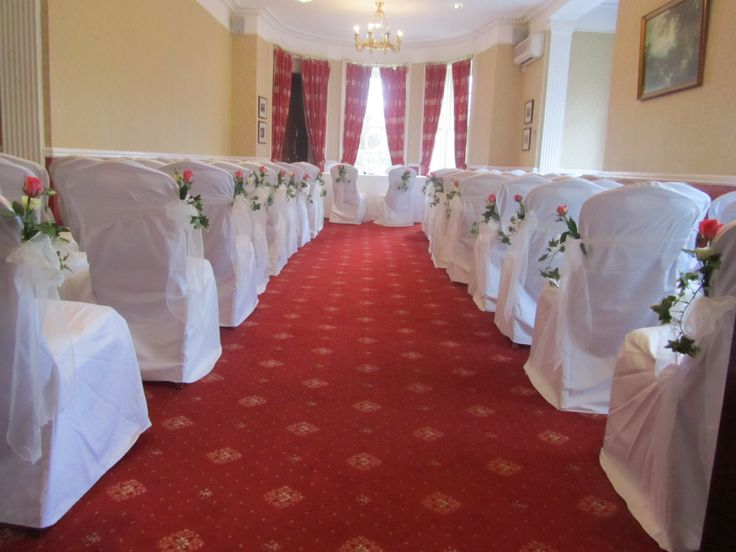 A beautiful ceremony room decorated with chair covers, Ivory sashes and flowers on the aisle chairs