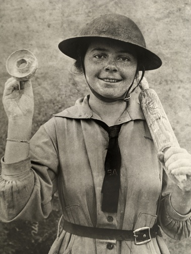A woman in the Salvation Army holds up a mold for backing donuts