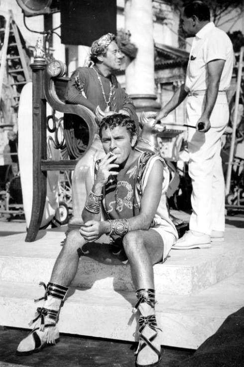 "Richard Burton taking a smoke break, while co-star Rex Harrison and director Joseph Mankiewicz chat behind him on the set of ""Cleopatra"" in 1961."