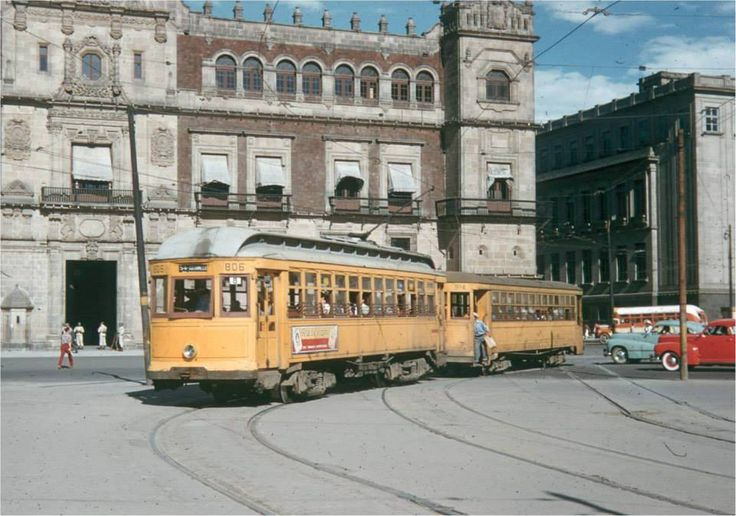 Un par de tranvías pasan frente al Zócalo capitalino en la década de los cincuenta. A la izquierda se aprecia el Palacio Nacional, y del lado derecho, la sede de la Suprema Corte de Justicia.