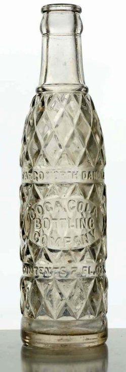 A Coca-Cola Fargo, North Dakota clear embossed glass soda bottle, circa 1920s to 1930s, 7 oz [diamond pattern embossed Coca-Cola Bottling Company].