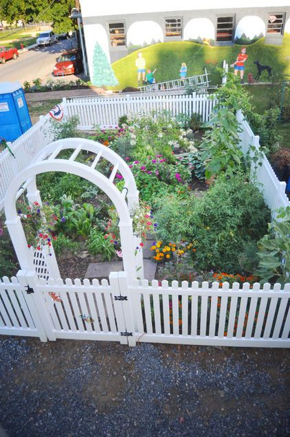 White picket fence around edible garden.  We need this, since the dog likes to eat the veggies before I can pick them!