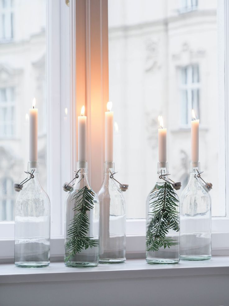 glass bottles filled with water and evergreens, and a candle on top