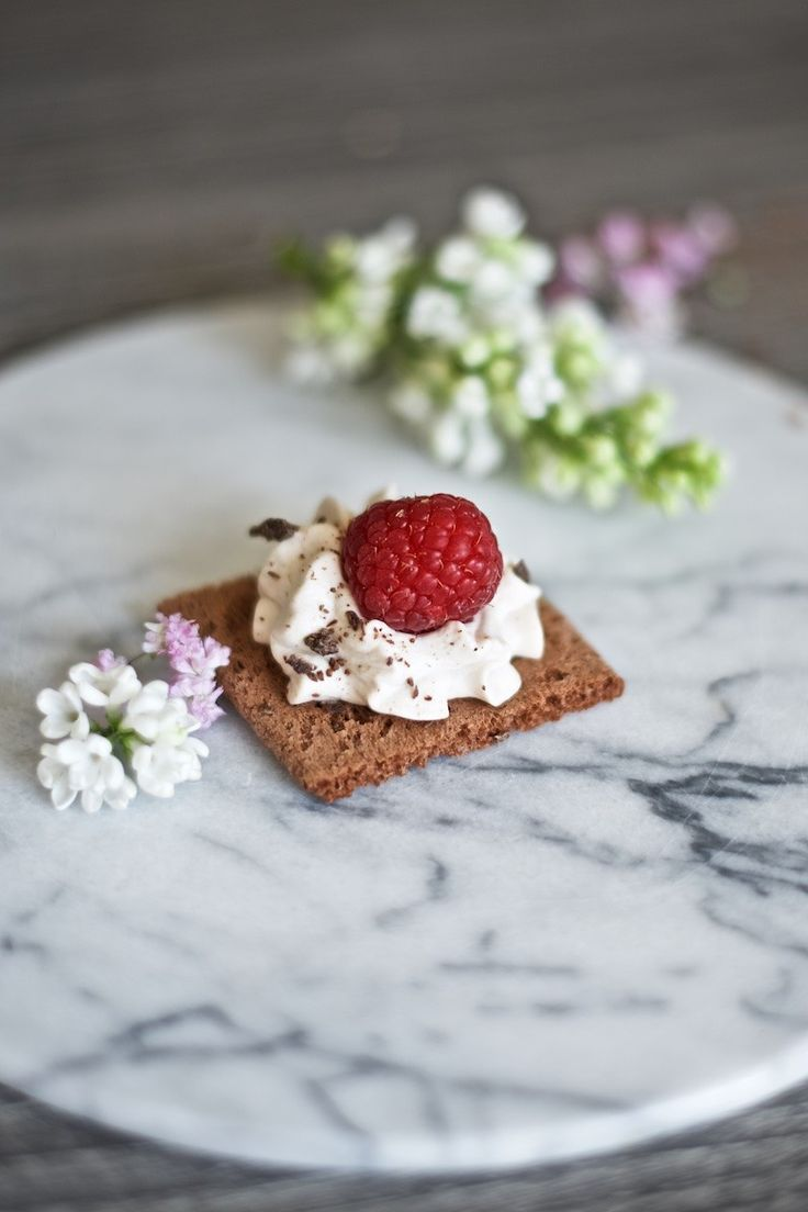 Gluten-free chocolate cookies with oat cream cheese filling and fresh berries.