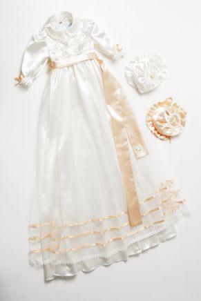 Dåpskjole Aurora er en nydelig dåpskjole i offwhite sateng med detaljer i aprikos.  Dette er en romantisk offwhite  dåpskjole i sateng, kombinert med tyll og satengbånd i aprikos. Nydelig dåpslue og pompadur medfølger til denne dåpskjolen.