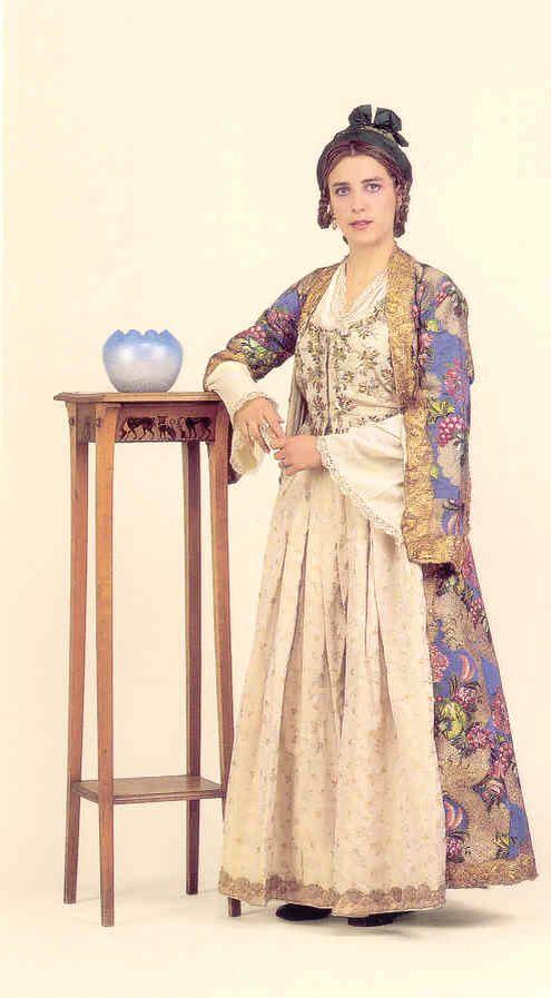 Λυκειο Ελληνίδων Φορεσιά από την Σιφνο. 18ος αιώνας. Το χρυσοφόρο στην αρχαιότητα νησί, φημισμένο για τους κεραμείς του, δεν θα μπορούσε να μη διακρίνεται από μια «χρυσή» φορεσιά. Η γυναικεία φορεσιά της Σίφνου αποτελείται από μια έσω βράκα, το λεγόμενο «μισοφόρι» ή «μεσοφούστανο». Ακολουθεί ένα λεπτό υποκάμισο,άσπρου χρώματος με ωραίο τελείωμα και κέντημα . Τη λινή και σταμπωτή φούστα τη λένε «καναλωτή» (επειδή έκανε κανάλια, λούκια). Αμάνικο γιλέκο, από λινό σταμπωτό, που δένει μπροστά με…
