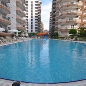 Complex is located in Mahmutlar, 125 meters away  to the Beach and 14 km  from Alanya. It consist of 3 Blocks and apartment is on the 4. floor of 10 storey building. Walking Distance to everything you need in your daily life. 2 Bedroom apartment is 120 m2 with open plan kitchen, living room, 2 bathroom, 2 balconies.