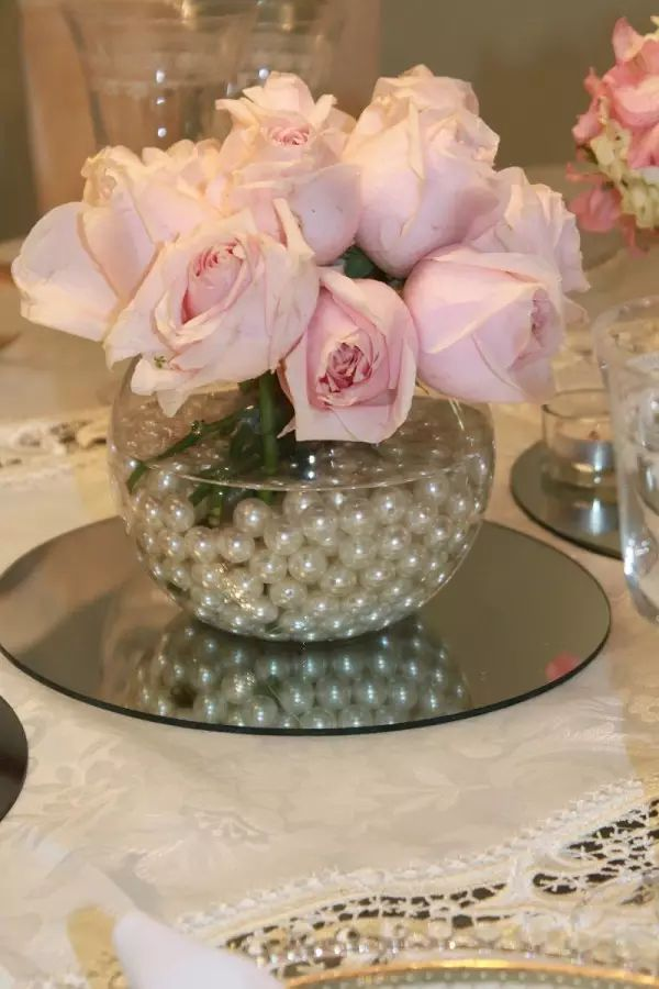 Peach/pink roses 🌹 with pearls for a centerpiece just a tip with a stout vase after fill with water and pearls use Saran Wrap ( just enough) to cover and poke the stems through the flowers will stay in place through out the occassion