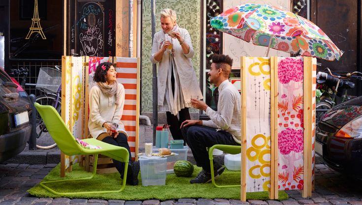 IKEA Österreich, Ein Außenbereich auf einem Parkplatz, u. a. mit LOCKSTA Sesseln in Grün, langflorigen HAMPEN Teppichen leuchtend grün, transparenten SAMLA B...