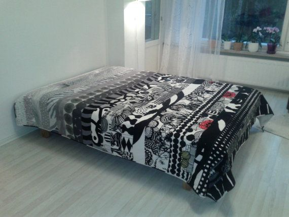 Modern quilt made from Marimekko fabric in black, grey and white. Scandinavian patchwork contemporary bed cover. The colors are progressing from light grey/white through black/white to almost black towards the bottom of the quilt. It is machine pieced and hand quilted in simple straight